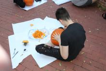 Male student carving pumpkin