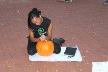 Female student carving pumpkin