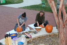 Two female students carving pumpkins by a tree
