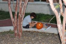 Student carving pumpkin