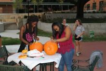 Students carving pumpkins on a table