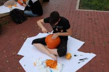 Student carving a pumpkin on the ground