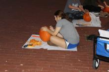 Students carving pumpkins at night