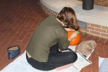 Student carving a pumpkin at night