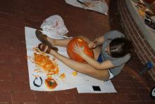 Student carving pumpkin at night