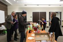 People surrounding a pancake toppings table