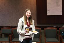 A student holding coffee and a bagel