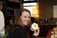 A student smiling and holding a bagel