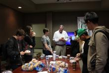 Dr. Duban talking to students getting bagels