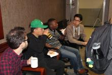 Sean talking to students while drinking coffee
