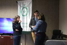 Students having a conversation by the Honors College banner