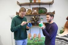 A couple of male students painting pots in front of a supply table