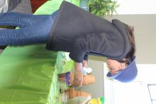 A girl painting purple designs on her pot