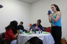 Several students painting pots around a table