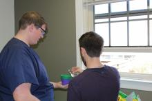 A couple of students pouring water into a pot