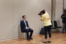 A student in a suit getting his photo taken in the ballroom