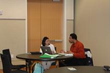 A staff member discussing a paper with a student