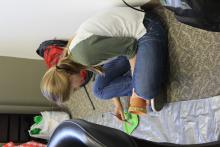 A girl sitting on the ground while painting her pot