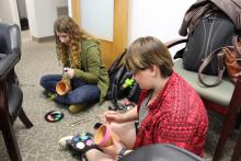 A couple of students sitting on the floor and painting their pots