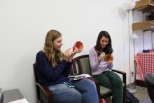 A couple of students sitting and chatting while painting their pots