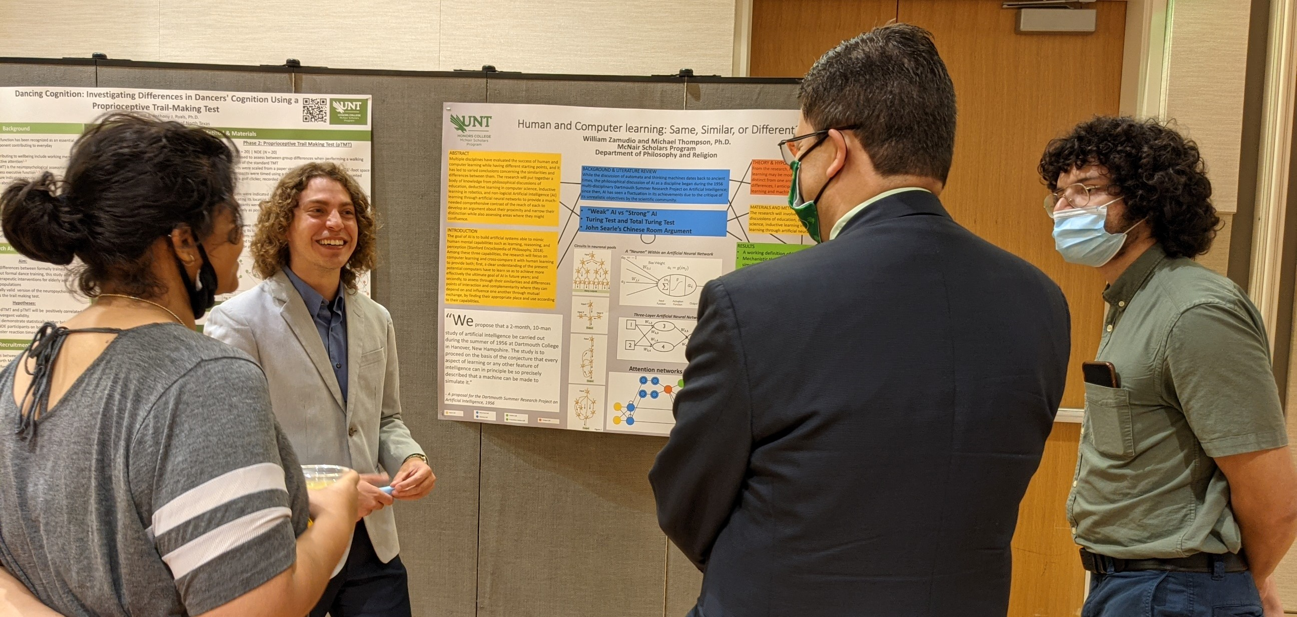 Scholar discussing research with attendees at fall assembly