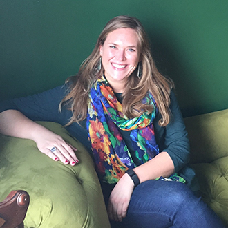 Photo of Kelsey Jistel sitting on a green couch